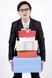 Asian bussiness man with stack of gifts. Smart businessman with glasses carrying heavy gifts Stock Photos