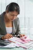 Asian bussinesswoman checking bills Royalty Free Stock Photo