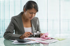Asian bussinesswoman checking bills Stock Image