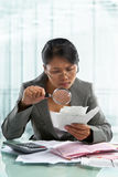 Asian bussinesswoman checking bills Stock Photo