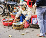 Asian buyer and trader selling fresh fish in street market Stock Images