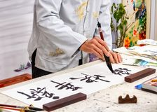 Asian caligraphy. The master of Chinese Caligraphy writes on rice paper characters and hieroglyphs that read Xin nian stock photo