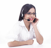 Asian call centre girl. Wearing a white shirt and with headphone stock photography