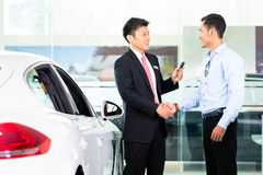 Asian Car Salesman selling auto. To customer Royalty Free Stock Photography