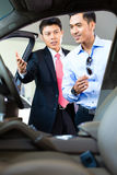 Asian Car Salesman selling auto to customer. In dealership Royalty Free Stock Photo