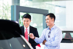 Asian Car Salesman selling auto to customer. Asian Car Salesman showing automobile to customer Royalty Free Stock Images