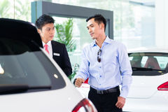 Asian Car Salesman selling auto to customer. Asian Car Salesman in showroom selling auto to customer Royalty Free Stock Photos