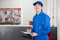 Asian car technician smiling in garage service Royalty Free Stock Photo