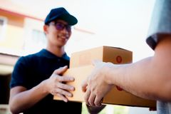 Asian cargo carrier holds a cardboard box with the package inside and the recipient is signing the package stock photography