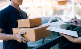 Asian cargo carrier holds a cardboard box with the package inside and the recipient is signing the package.  royalty free stock photography