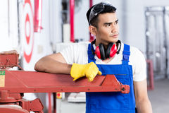 Asian carpenter with electric saw in workshop. Standing on a machine Royalty Free Stock Photography