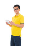 Asian casual male using a tablet surfing. Photo Stock Photos