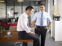 Asian and caucasian colleagues talking in office Stock Photography