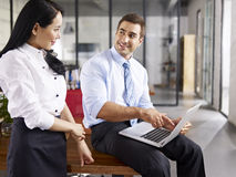 Asian and caucasian colleagues talking in office Royalty Free Stock Photography