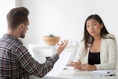 Asian and caucasian partners negotiating disagreeing about contr. Asian and caucasian partners negotiating on contract terms at meeting, chinese businesswoman Stock Photos