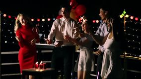 Asian and Caucasian people in roof top party. Asian Caucasian people dancing and holding bottle of alcohol in their hands, balloon and ornamental lights behind