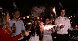 Asian and Caucasian playing sparklers and dancing. Group of Asian and Caucasian people, playing sparklers and dancing, concept for new year party