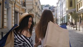 Asian and caucasian shopper friends smiling at cam stock footage