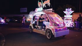 Two women and man riding bling bling car in Jogja. Asian and caucasian young happy women and man riding with shopping bags in bling bling illuminated peddle car stock footage