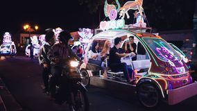 Two women and man riding bling bling car in Jogja. Asian and caucasian young happy women and man riding with shopping bags in bling bling illuminated peddle car stock video