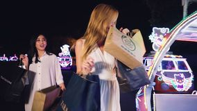 Two women walking at bling bling cars square. Asian and caucasian young happy women walking with shopping bags at bling bling illuminated peddle cars Alun-Alun stock video footage