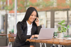 Asian cheerful middle-aged businesswoman working at a cafe table. Asian middle-aged businesswoman sitting at a cafe table using a laptop computer and talking on Stock Image