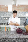 Asian Chef. Asian young chef crossing arms in his kitchen Stock Photography