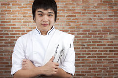 Asian Chef. Asian young chef crossing arms holding kitchen utensil Royalty Free Stock Photos