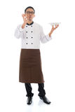 Asian chef holding a plate. Full body Asian chef holding an empty plate, showing tasty and satisfied hand sign, standing isolated on white background Royalty Free Stock Image