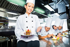 Asian Chef in restaurant kitchen cooking. Asian Indonesian chef along with other cooks in restaurant or hotel kitchen cooking, finishing  dish or plate for Stock Photography