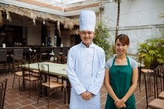 Asian chef and a waitress. Smiling Asian chef and a waitress standing in outdoor restaurant Royalty Free Stock Photo