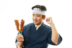 Asian chef with Yakitori. Portrait of an Asian chef in uniform Royalty Free Stock Image