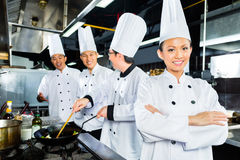 Asian Chefs in hotel restaurant kitchen. Asian Indonesian chefs along with other cooks in restaurant or hotel kitchen cooking or fry with a pan at the stove Royalty Free Stock Images