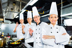 Asian Chefs in hotel restaurant kitchen. Asian Indonesian chefs along with other cooks in restaurant or hotel kitchen cooking or fry with a pan at the stove Royalty Free Stock Photo