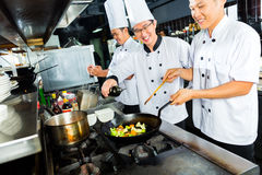 Asian Chefs in restaurant kitchen cooking. Chefs in Asian Restaurant or Hotel kitchen cooking and finishing dishes Stock Images