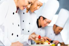Asian Chefs in restaurant kitchen cooking. Asian Indonesian chef along with other cooks in restaurant or hotel kitchen cooking, finishing dish or plate for Stock Photos