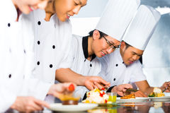 Asian Chefs in restaurant kitchen cooking. Asian Indonesian chef along with other cooks in restaurant or hotel kitchen cooking, finishing dish or plate for Stock Photo
