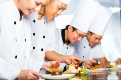 Asian Chefs in restaurant kitchen cooking. Asian Indonesian chef along with other cooks in restaurant or hotel kitchen cooking, finishing dish or plate for Stock Image