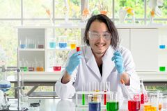 Asian chemist man checking liquid substance in test tubes stock images