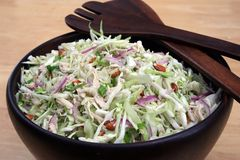 Asian Chicken Salad. In Dark Wood Bowl with Salad Tongs Stock Photo