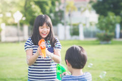 Asian chid Shooting Bubbles from Bubble Gun Royalty Free Stock Photo