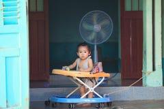 Asian child in baby walker. Phu Quoc island, Vietnam - December 31, 2014: vietnamese  toddler standing on traditional asian porch in baby walker Stock Photo