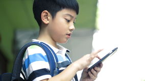 Asian child with backpack using a digital cell phone stock footage