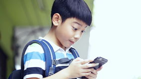 Asian child with backpack using a digital cell phone stock video