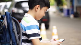 Asian child with backpack using a digital cell phone stock video footage