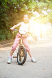 Asian child biking outdoor. Royalty Free Stock Photography