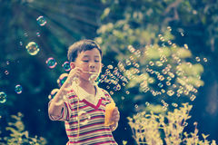 Asian child blowing soap bubbles, nature background. Vintage pic Royalty Free Stock Photo