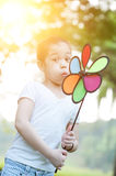 Asian child blowing windmill outdoors. Stock Photos