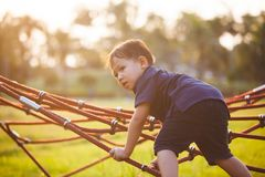 Asian child boy having fun to play and climbing on the rope stock photography