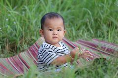 Asian child boy sit on Thai mat in the garden. Asian child boy sit on Thai mat in the garden,concept of learning and health Royalty Free Stock Photography